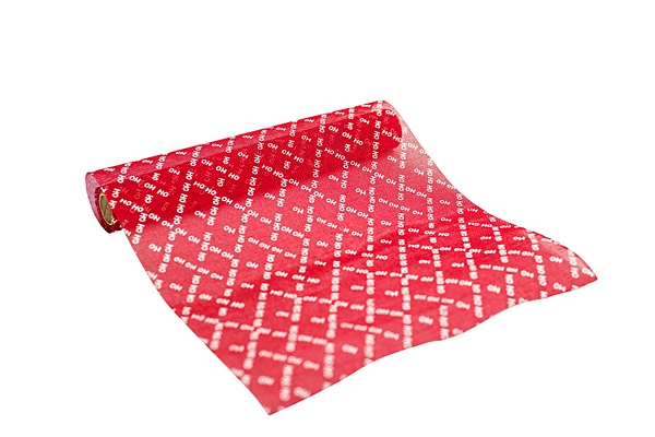 red christmas table runner on a roll with white words HOHOHO in a criss-cross pattern