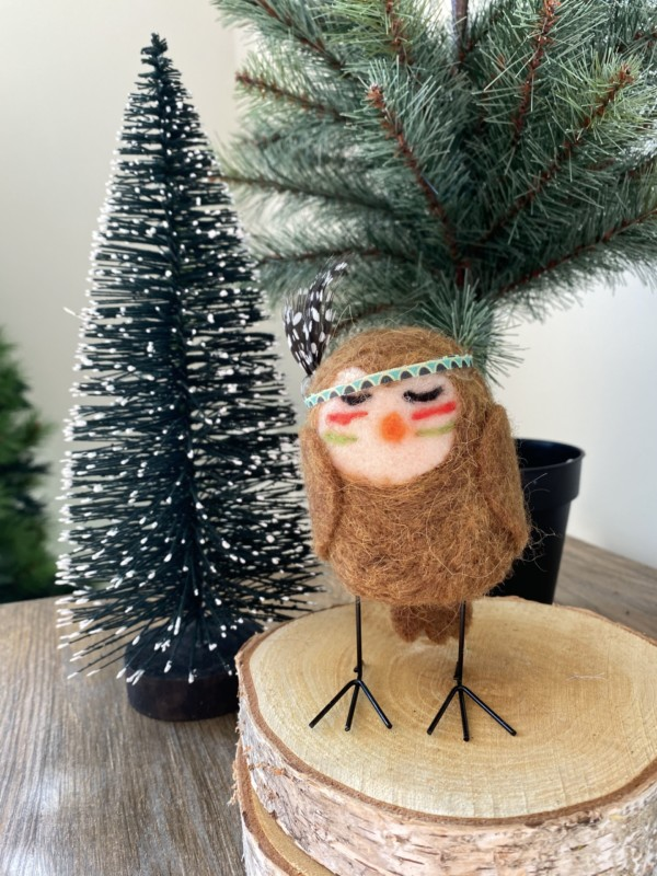 small felt owl standing on birch log pieces with christmas tree