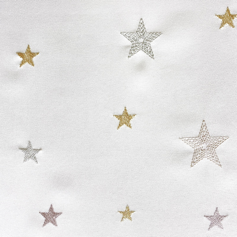 close of white tablerunner with embroidered stars