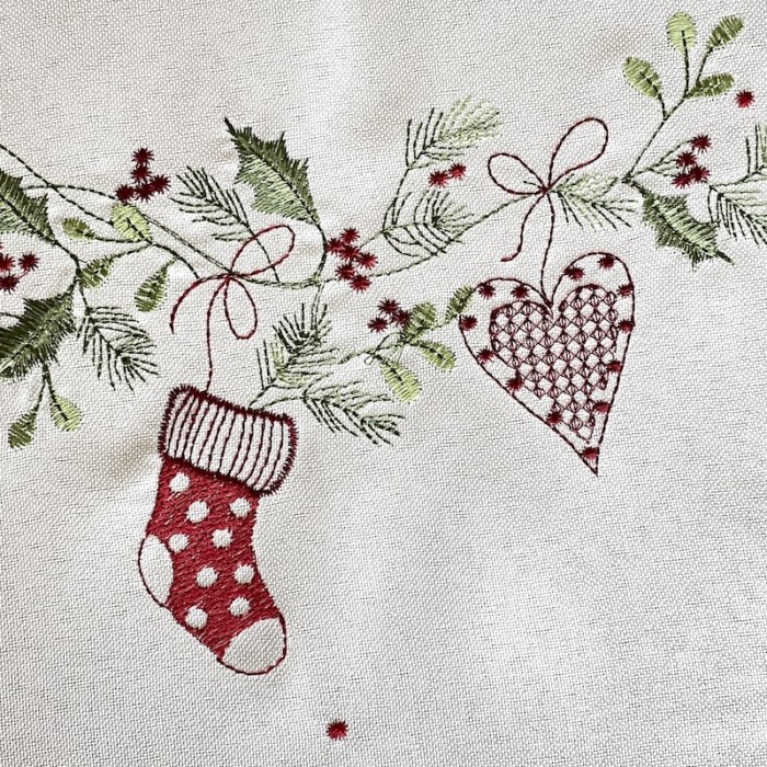 close up of embroidery on christmas tablerunner boot and heart