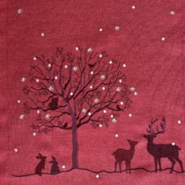 close up of dark red tblerunner embroidered with deer and a tree