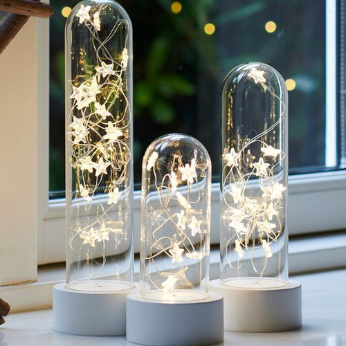 three glass cloches filled with LED lights