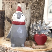 small grey wooden penguin with red heart on a sled