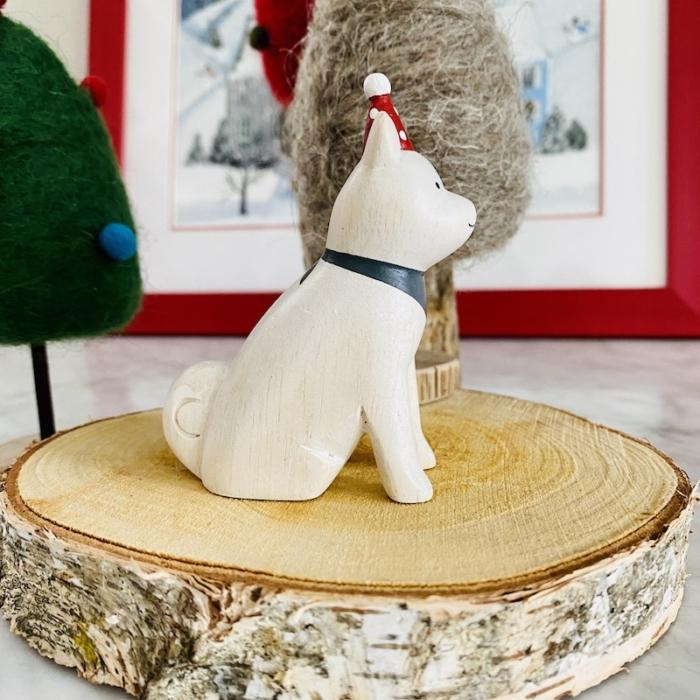 side view of white wooden akita dog waering red santa hat
