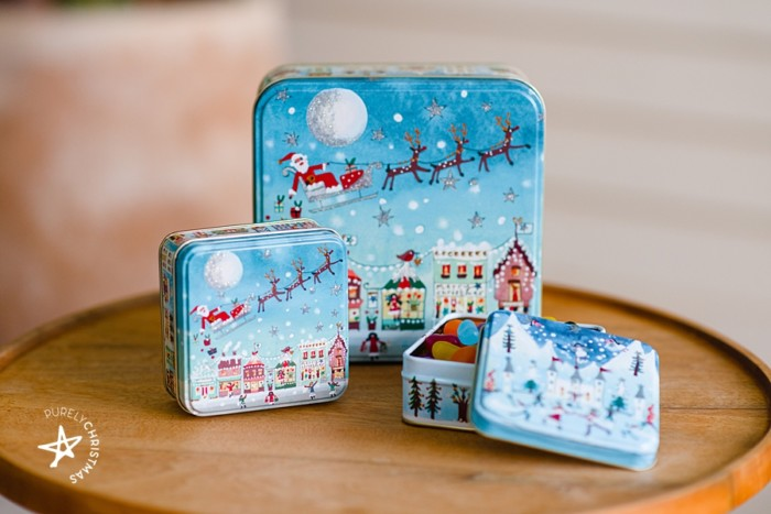 set of christmas tins on table with sleigh